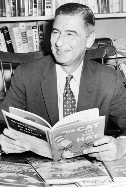 Picture of Dr Seuss. Ted Geisel (Dr. Seuss) half-length portrait, seated at desk covered with his books / World Telegram & Sun photo by Al Ravenna.